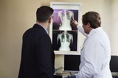 doctor-pointing-x-ray-result-beside-man-