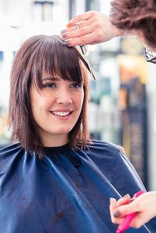 Hairdresser cutting woman hair in shop.j