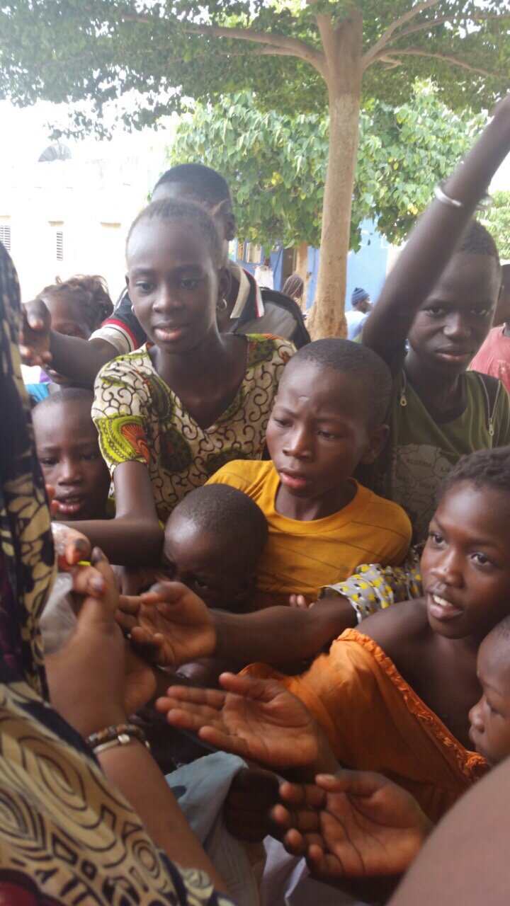 Village children receiving snacks in Kaolack, Senegal!