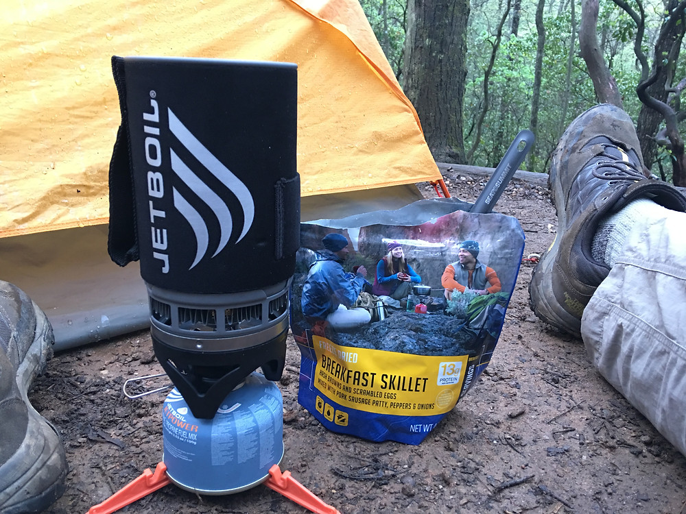 A JetBoil stove set up on the ground outside of a tent.