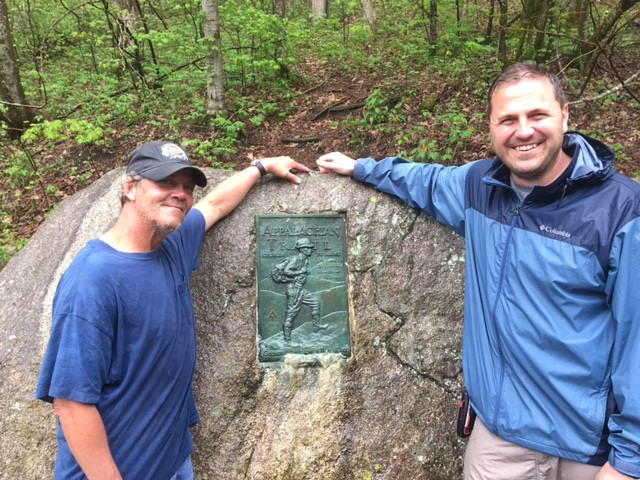 Hikers next to Appalachian Trail sign.