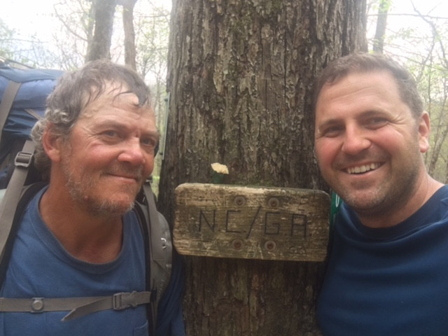Two men beside the NC/GA border sign on the Appalachian Trail.