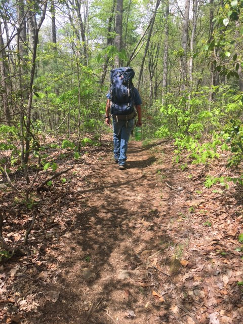 Man walking along trail with big backpack.