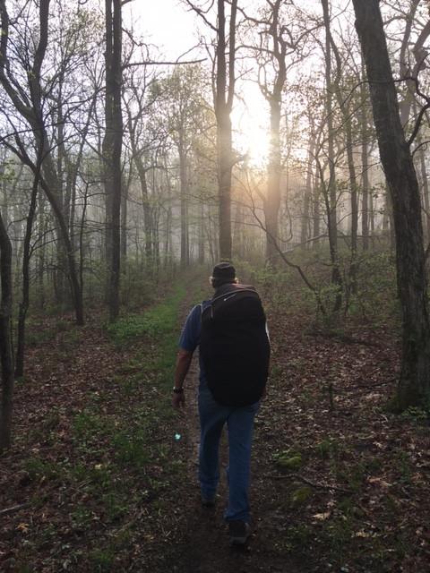 A backpacker walking along a trail going towards the sun.
