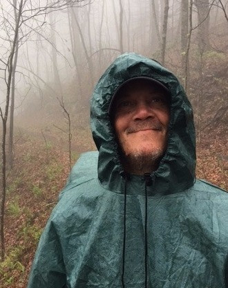 Homeless man dressed in raincoat pulled tight around face hiking on Appalachian Trail.