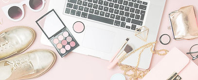 personal style coach workspace with silver laptop and makeup and accessories on a pink background