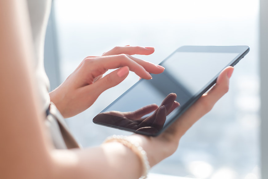 Close-up photo of female hands working with tablet computer. Woman using social network, t