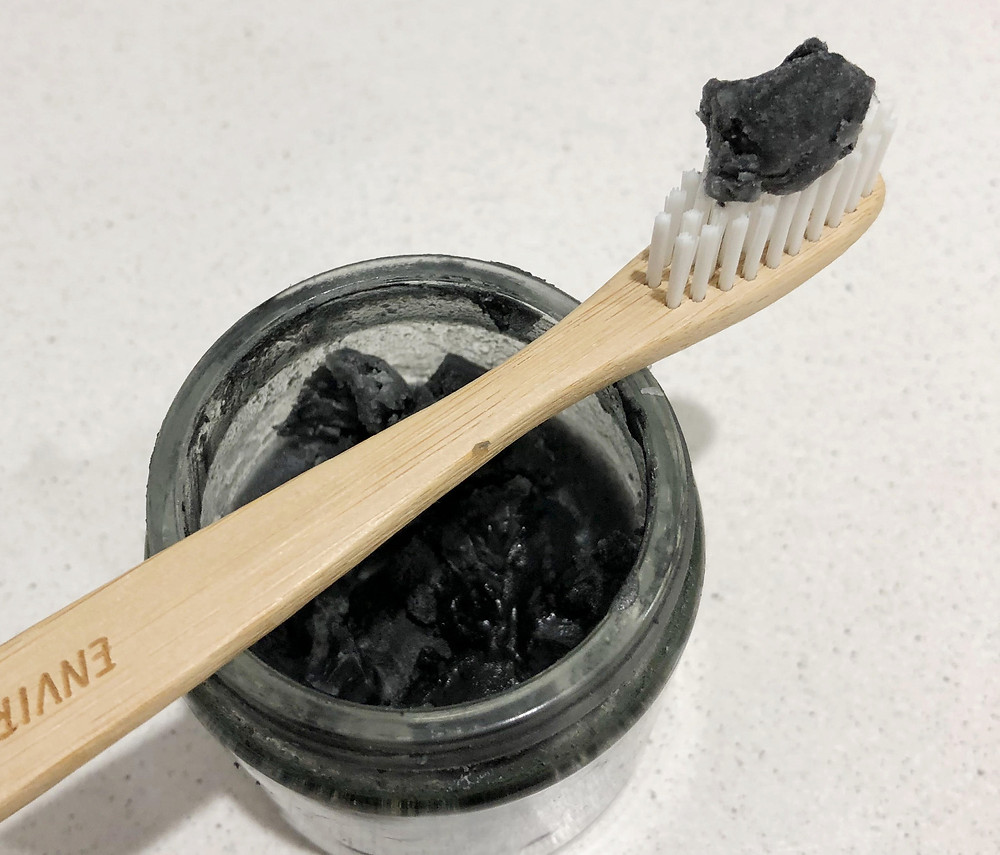 DIY chargoal toothpaste in glass jar with bamboo toothbrush