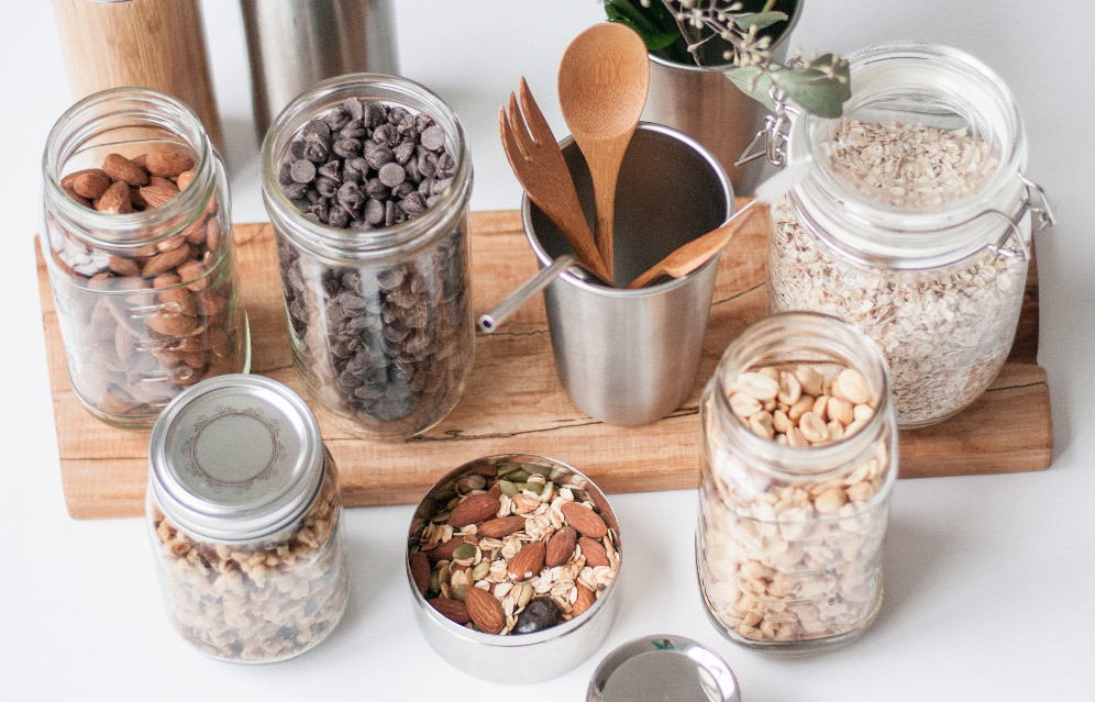 Dry bulk foods in jars with stainless steal cup and containers, bamboo utensils, and stainless steal straw.