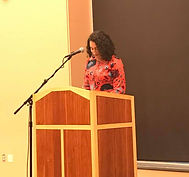 Yael Massen reading at a podium