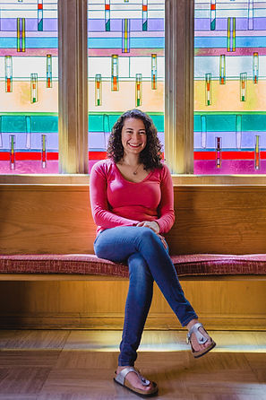 Photo of Yael Massen smiling in front of a stained glass window.