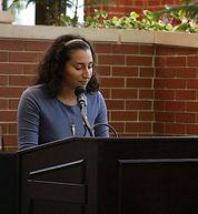 Yael Massen speaking at a podium