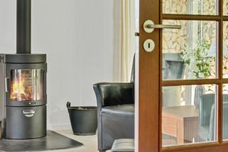 Moderne_bæredygtig_brændeovn_komplimentere_designet_fra_50er_villaens_rustikke_lyse_stue