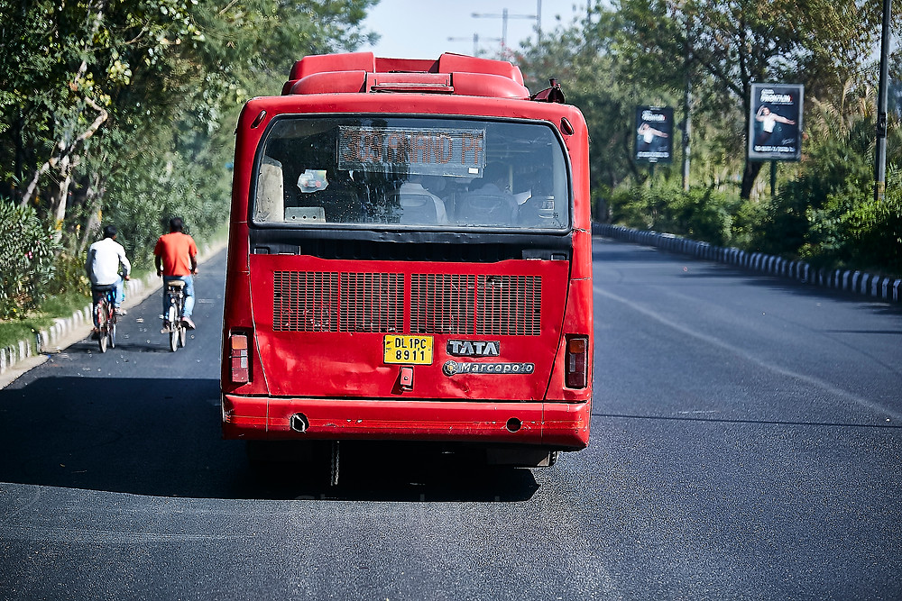 low for bus on delhi road with two cycle riders