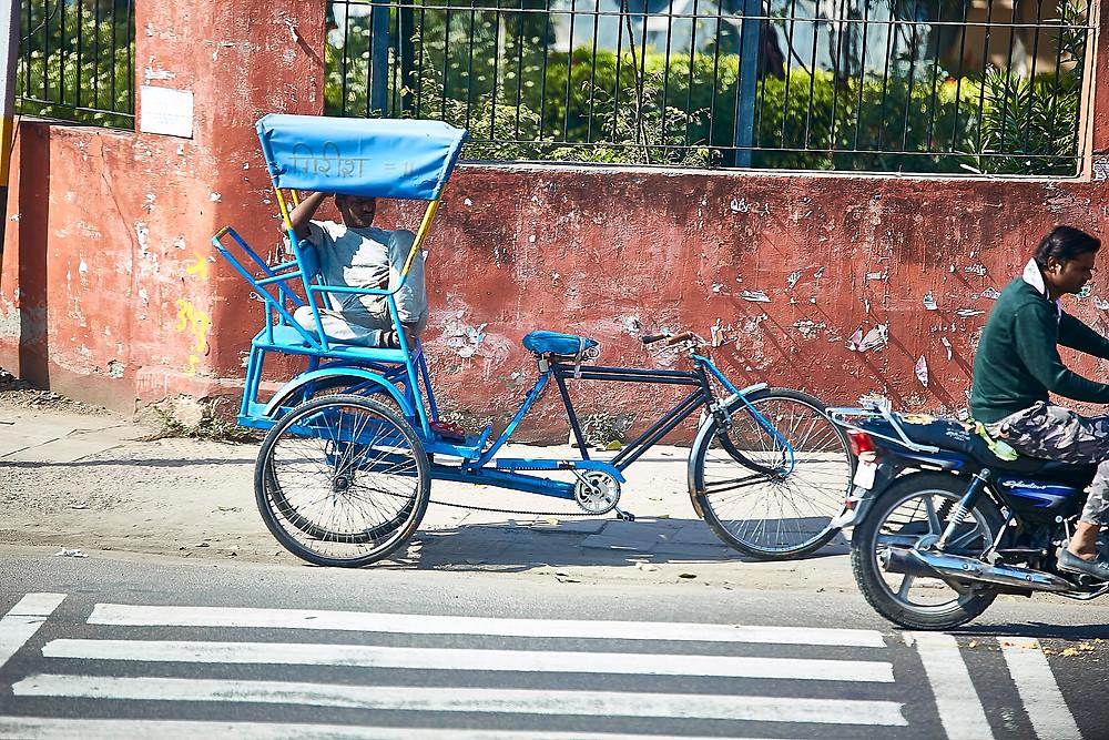 man pull rickshaw parked on footpath a bike going