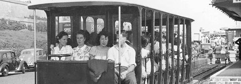 People grouped together sitting on Volk's Electric Railway carriage