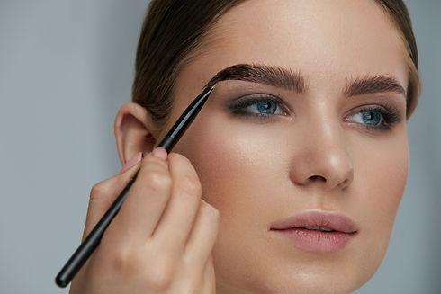 Eyebrow coloring. Woman applying brow ti
