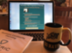 """Artistic image of a """"Go Navy"""" coffee cup on a laptop that has Soteric Group LLC's Business Continuity Planning page displayed. A binder with a cover sheet showing the Soteric Group logo and coversheet for a Business Continuity Plan can also be seen."""