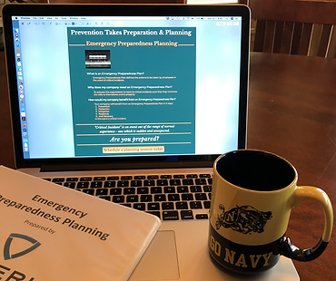 """Artistic image of a """"Go Navy"""" coffee cup on a laptop that has Soteric Group LLC's Emergency Preparedness Planning page displayed. A binder with a cover sheet showing the Soteric Group logo and coversheet for an Emergency Preparedness Plan can also be seen."""