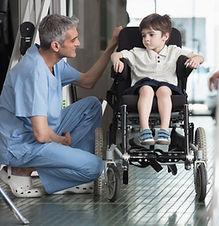 Docteur parlant à un garçon en fauteuil