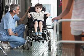 Doctor hablando con niño en silla de rue