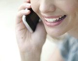 A woman smiles while talking into a phone that she holds up to her ear.