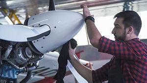 Bearded man polishing airplane propeller