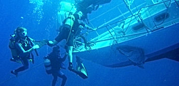 scuba divers with lift bags on a sail bo