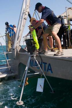 Lowering sonar equipment.
