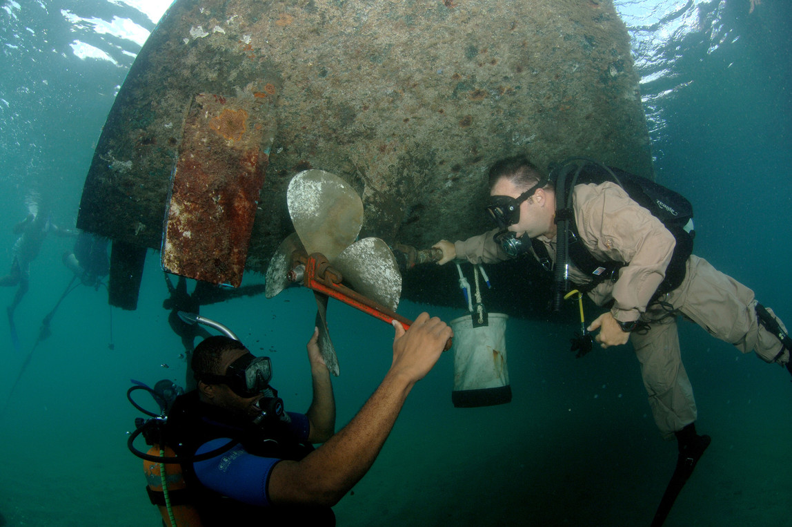 Salvage scuba divers removing a propelle