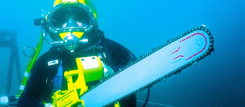 scuba diver with an underwater chain-saw