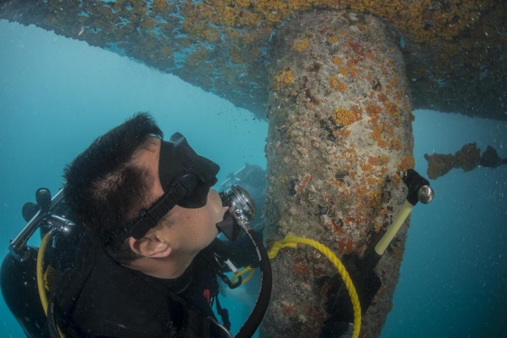 Salvage scuba diver under a boat.jpg