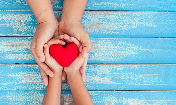 Red heart in child kid and mother hands