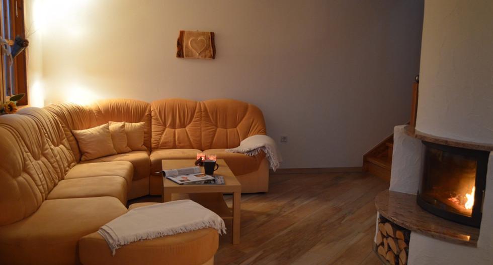 Sofa vor Kamin im Ferienhaus Sonnenblick