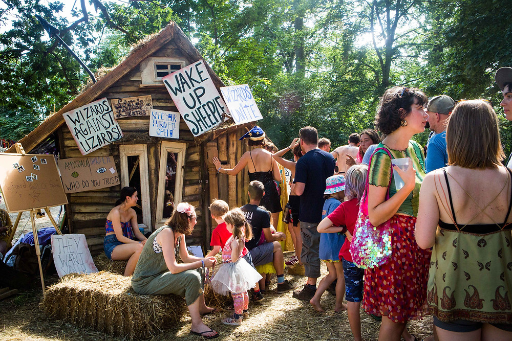 A queue of people standing outside a wizard's shack adorned with signs such as 'wake up sheeple' and 'wizards unite'