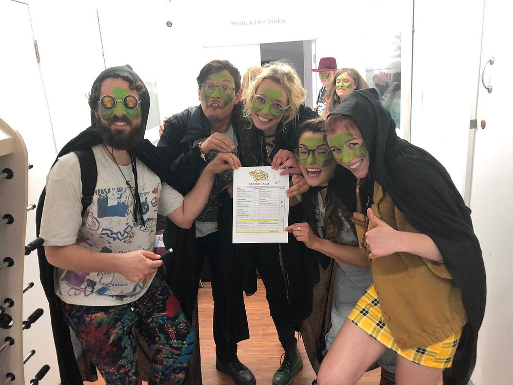 A group of 5 people with green face paint and black cloaks holding up a score card and smiling.
