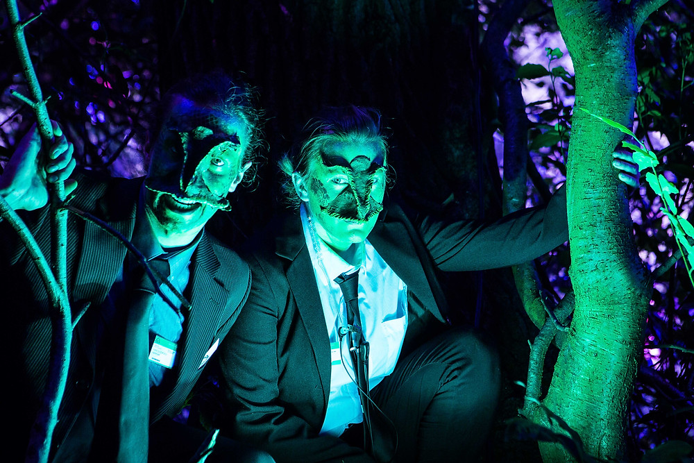 2 actors with Lizard face prosthetics, green face paint and suits in a woodland at night