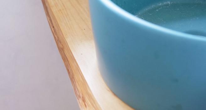 ヒノキの耳付き板に丸いボールをのせた洗面台。