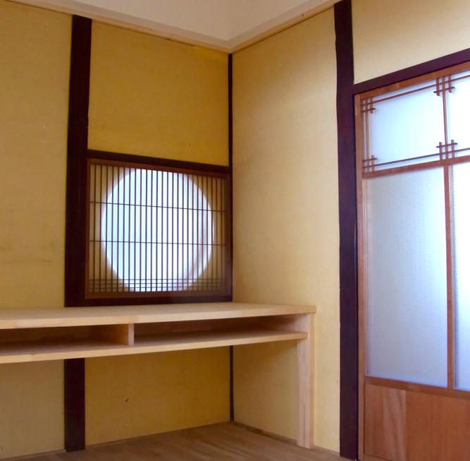 家事室につくったテーブルと丸窓。狭い部屋なので天井をなるべく高く、斜め天井にしました。