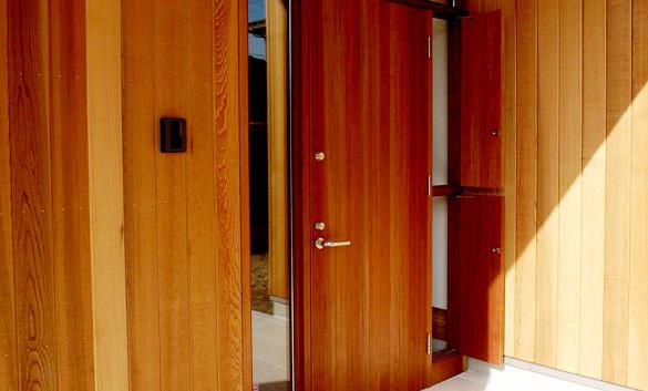 玄関の扉もレッドシダー。建具屋さんに幻のように残っていた古い材料を使わせてもらいました。扉の左右は光取りのガラスと通気の窓。