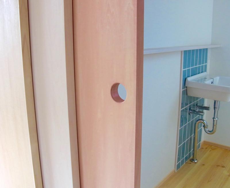 ピンクの扉の向こうには洗面。ここのタイルもアクセントカラーで。