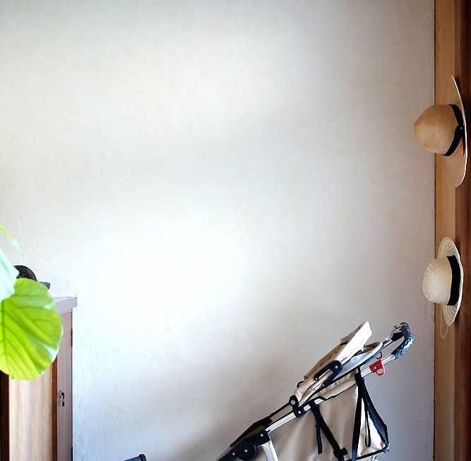 既存の綿壁(繊維壁)を削り取り、漆喰を塗ると暗かった玄関が明るく。白色の力を実感。