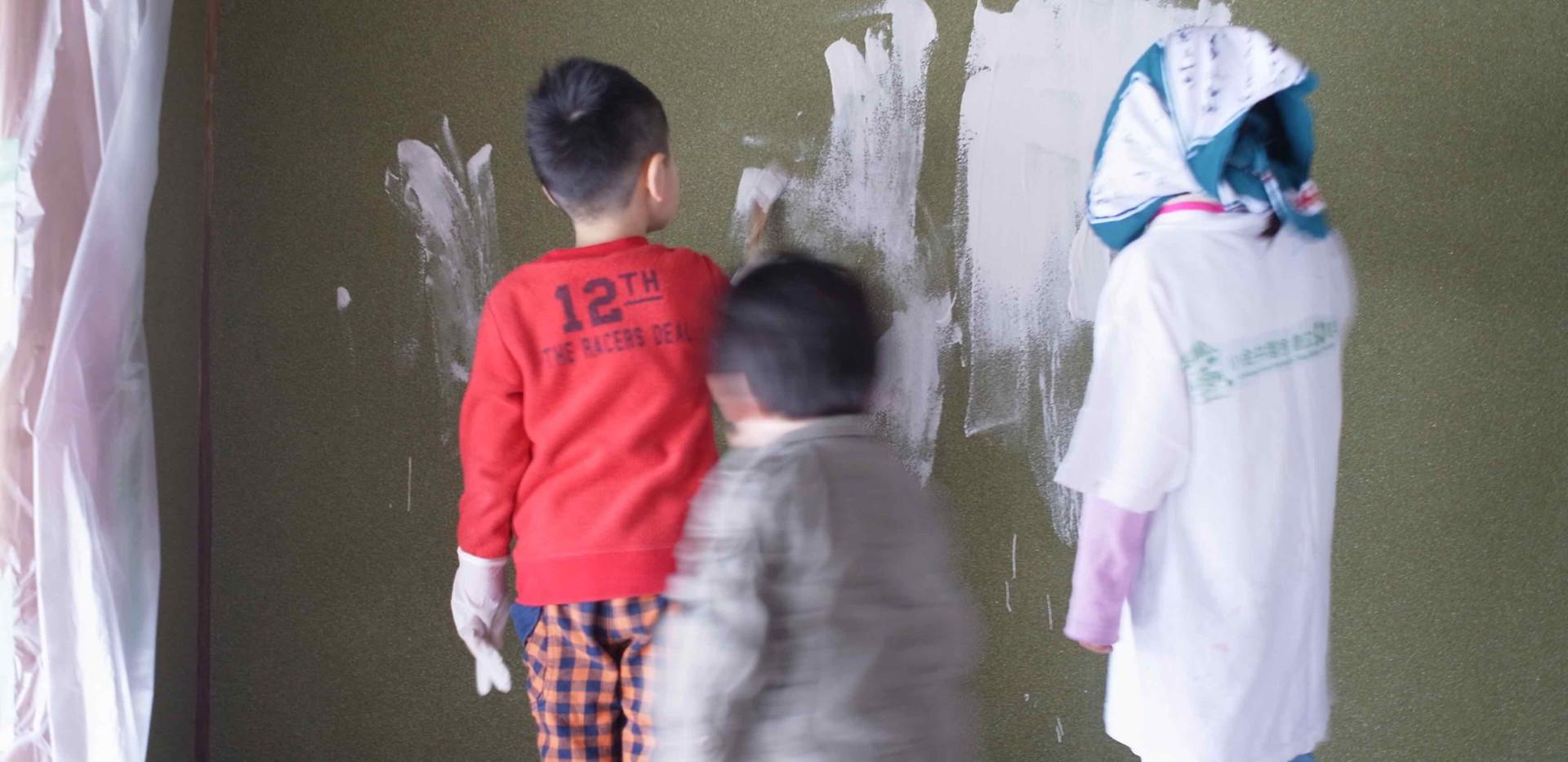 うぐいす色の壁を白い漆喰で塗り重ねます。こどもたち大活躍。