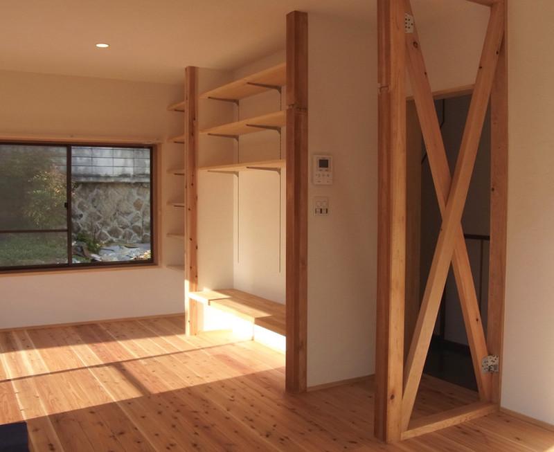 押入れと床の間だった部分に棚をつけ壁一面の収納。かつての面影、筋交いを残しつつLDKをワンルームに。