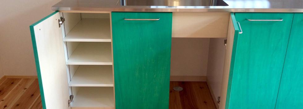 扉の中は可動棚という簡単な作り。シンク下はゴミ置き場。カウンターはそうじもしやすいステンレス一体加工。