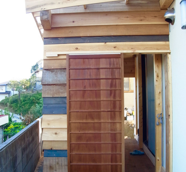 キッチンストーブのある玄関小屋。外壁材、扉ともブリコラージュ的に。