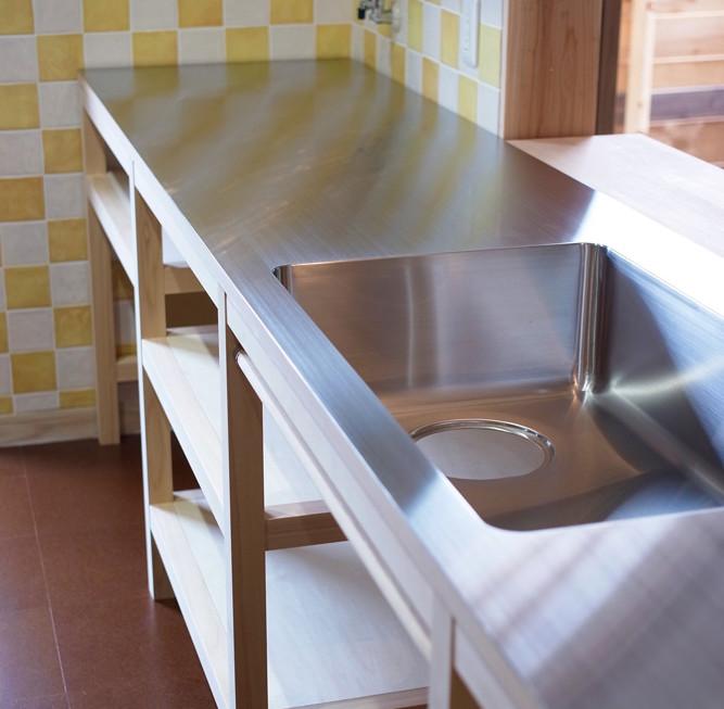 木で骨組みを組み、その上に2mのステンレスをシンクも一体で曲げ加工した板を貼るという何とも潔いキッチン。タイルも愛おしく。