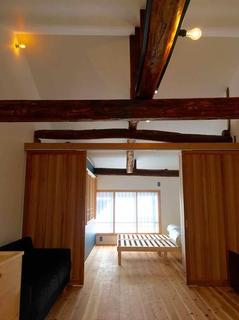 手前がリビング、奥がベッドルーム。杉板の引き戸で仕切っていますが上はつながっているのでワンルーム。