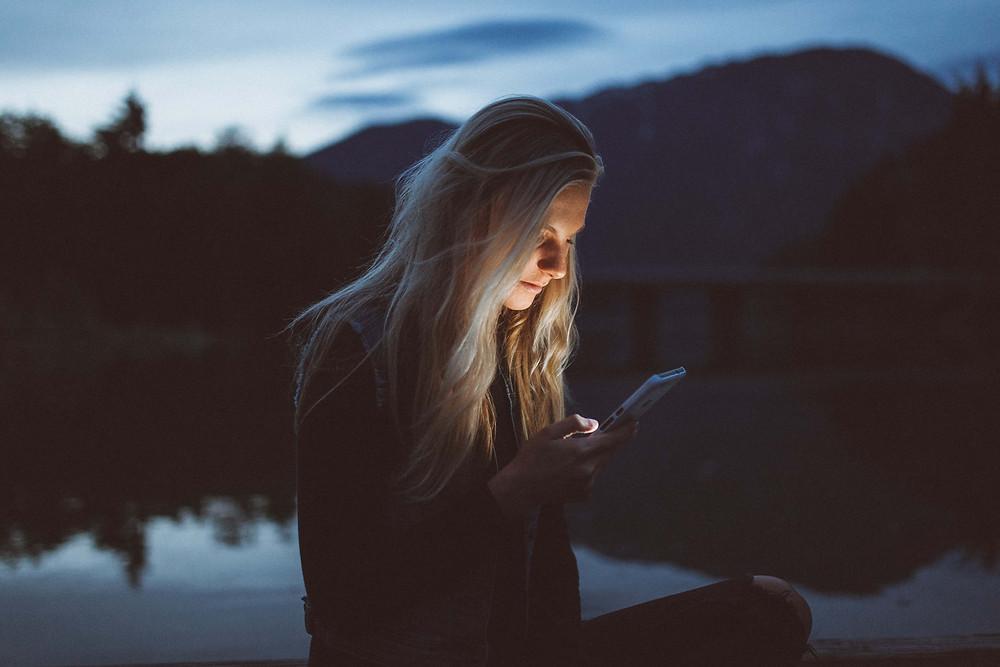person looking at phone at night