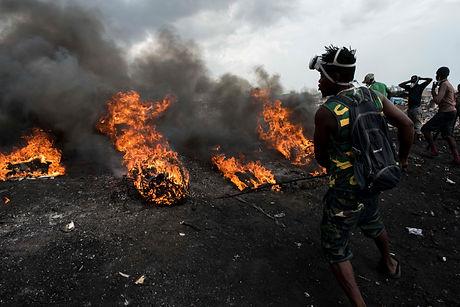 電化製品を燃やし中の金属を取り出す焼き場の若者.jpg